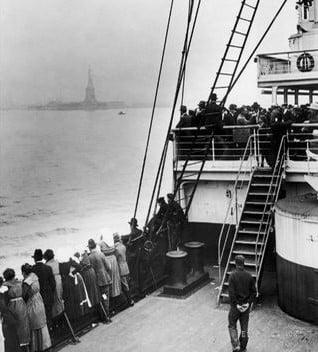 Imagen de inmigrantes llegando a Estados Unidos con la Estatua de la Libertad de fondo